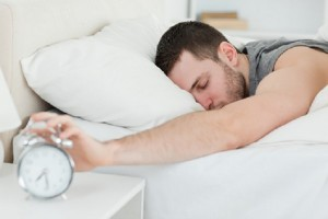 Sleeping man being awakened by an alarm clock