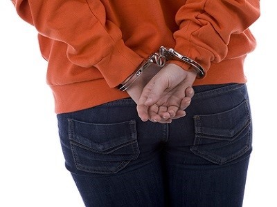 Standing backwards woman in handcuffs