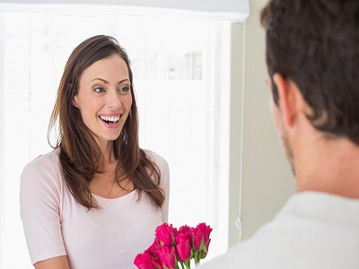 Cheerful young woman looking at man with flowers at home