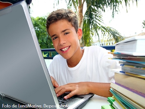 Happy teenager student boy working laptop