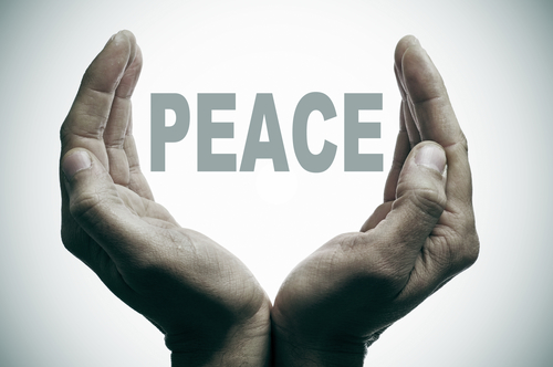 word peace between man hands forming a cup