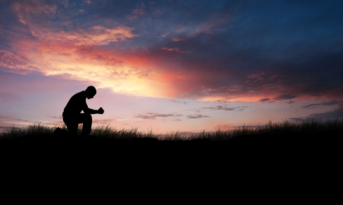 Man kneeling down in a field to pray