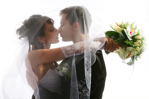 Wedding portrait of kissing just married young couple of groom and bride