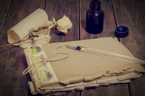 Composition in retro style: old battered notebook, ink bottle, pen, dried rose and a yellowed sheet of paper. Tinted photos