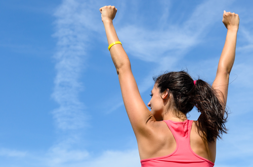 Woman from behind with arms raised expressing success towards sky on a sunny summer day.