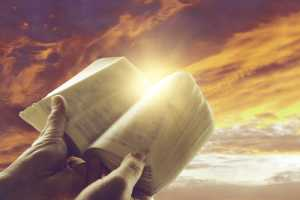 Hands holding open book in front of sky