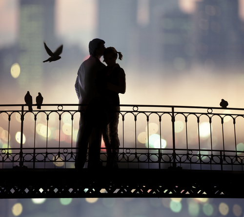 silhouette of bridge and pair of lovers on city background