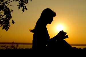 silhouette of a girl praying with the Bible