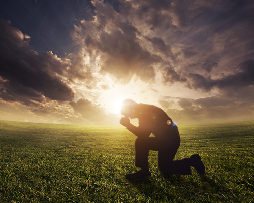Silhouetted man praying at sunset