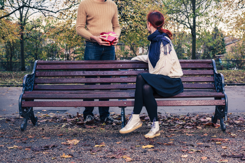 A young man is meeting a woman in the park and is giving her a lovely gift