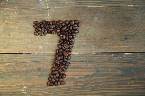 Number seven made with coffee beans on a wooden plank