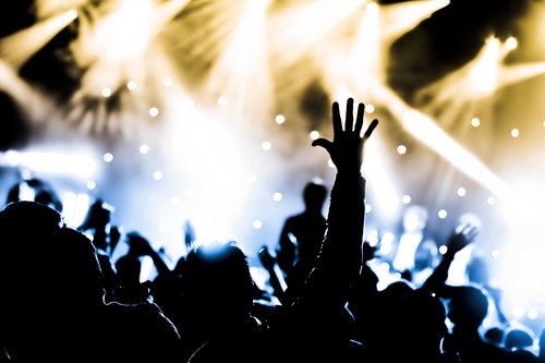 Crowd cheering with hands raised at a live music concert