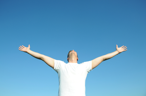 Young man in white t-shirt arms open, blue sky. Above space for text or graphics.