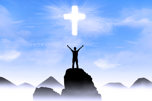 Silhouette of a man with arms stretched out to the cross glowing in the sky.