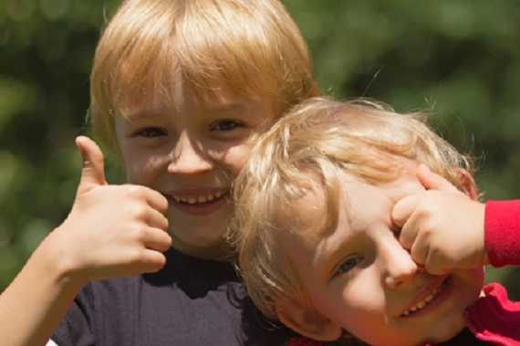 "Two blond boys (brothers). One of them hides his eyes with his hand, the other shows a gesture ""OK""."